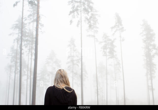 Sweden, Ostergotland, Woman in fog - Stock Image