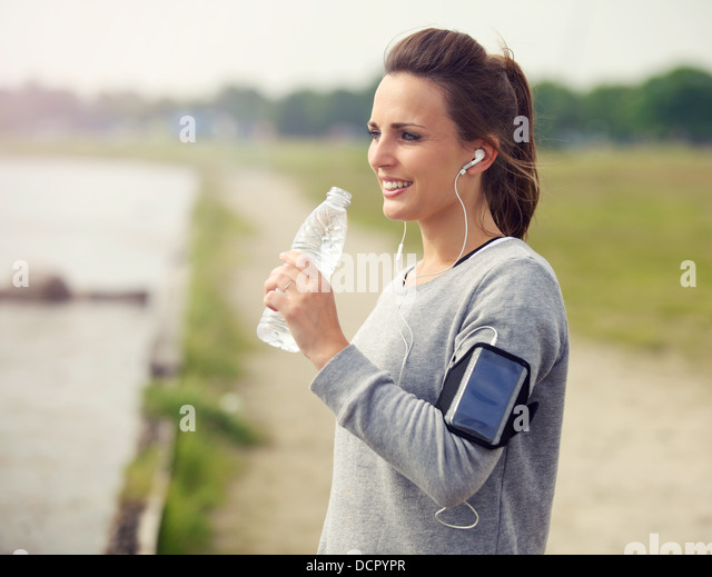 Female runner smiling while drinking bottled water - Stock Image