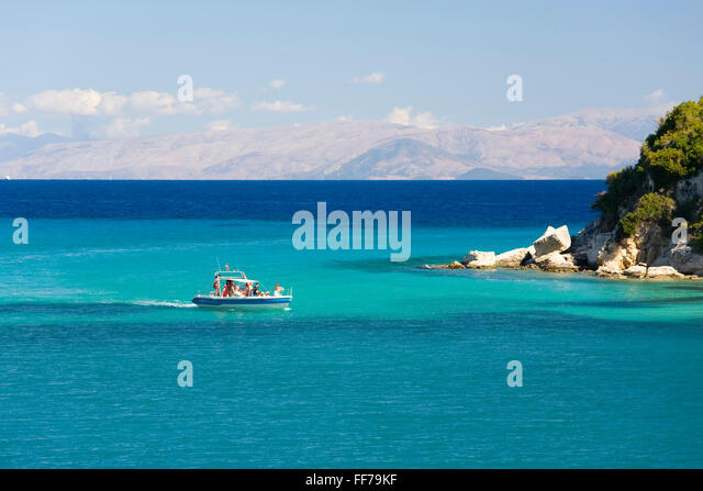 Lakka, Paxos, Ionian Islands, Greece. View across the clear turquoise waters of Lakka Bay, small boat arriving. - Stock Image