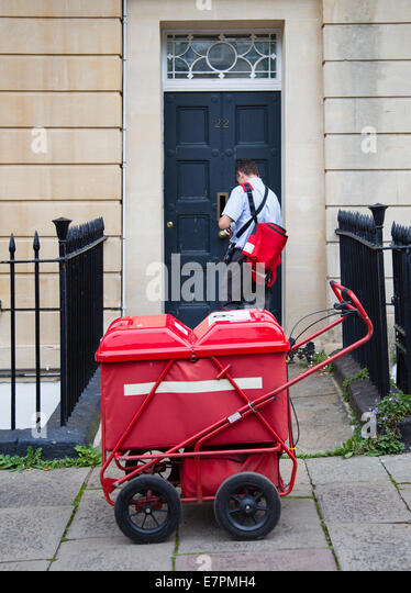 Postman delivering letter and mail through a Bristol house front door with the aid of a red mail cart - Stock Image