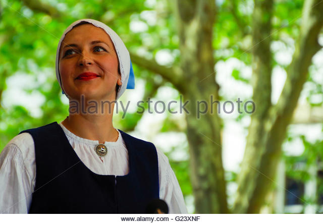 Beautiful woman in Estonian traditional costume smiling and looking up, portrait - Stock Image
