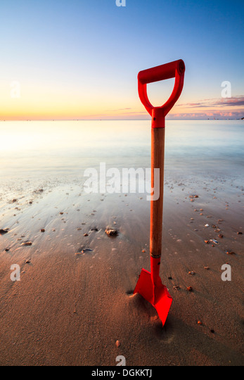 Spade in the sand on Swanage beach on a sunny morning. - Stock Image