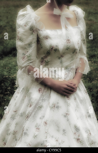 a woman with a period dress on a meadow - Stock-Bilder