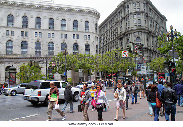 San Francisco California Market Street at Powell downtown street scene woman man pedestrians car traffic intersection - Stock Image