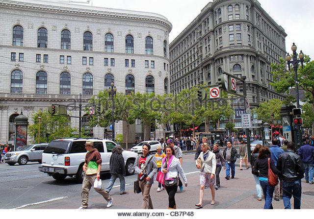 San Francisco California Market Street at Powell downtown street scene woman man pedestrians car traffic intersection - Stock Image