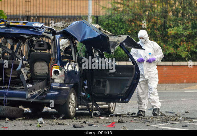 Belfast, Northern Ireland. 10th September 2013 - A PSNI forensics officer examines the wreckage of a vehicle which - Stock Image