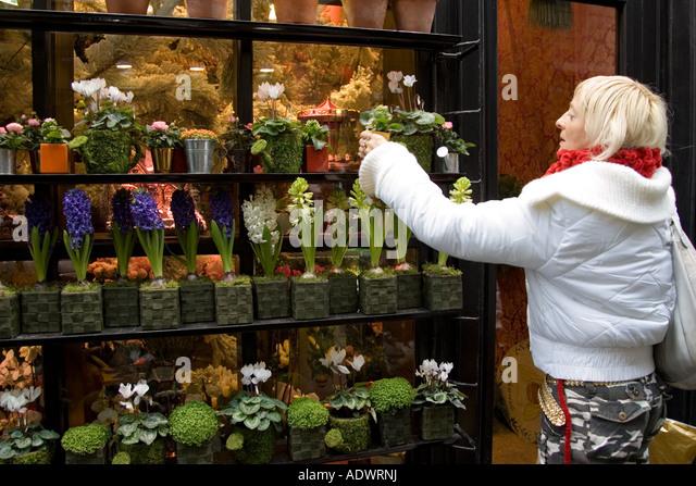 Woman visits florist shop and chooses plant near Boulevard Saint Germain Latin Quarter Paris France - Stock Image