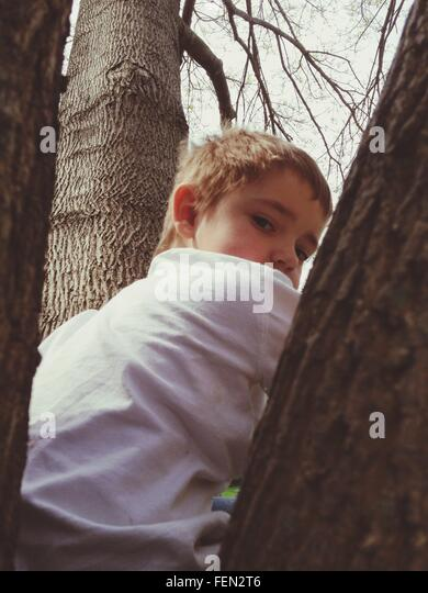 Portrait Of Boy Sitting In Park - Stock Image