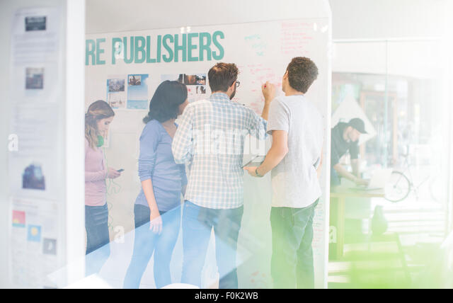 Publishers brainstorming at whiteboard in office - Stock Image