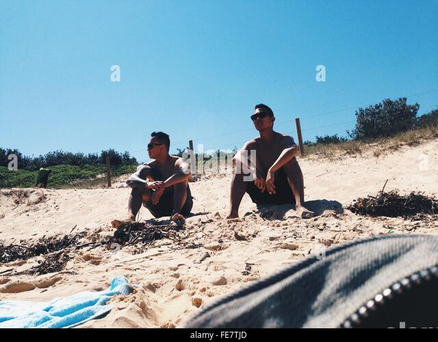 Low Angle View Of Friends Relaxing On Sandy Beach - Stock Image