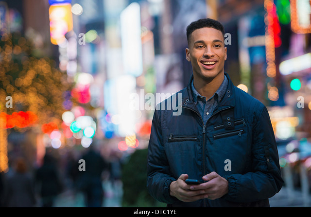 Young male tourist on busy street, New York City, USA - Stock-Bilder