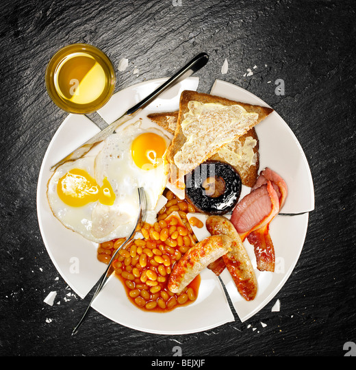 A full breakfast containing bacon, eggs, sausage, baked beans, mushroom and toast - Stock Image