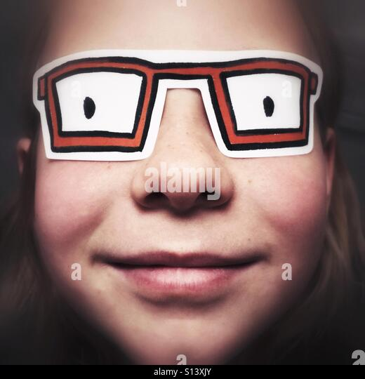 A closeup of a child with a sticker over her eyes that looks like glasses. - Stock Image