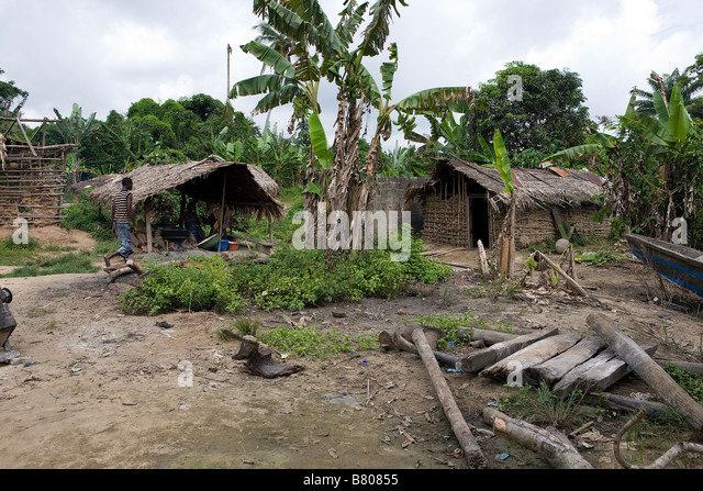A pile of scrap wood lay on the ground in front of wattle and daub houses in a remote stormy jungle village of Nigeria - Stock Image