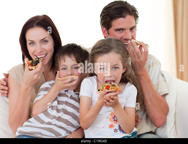 Happy family eating pizza - Stock Image