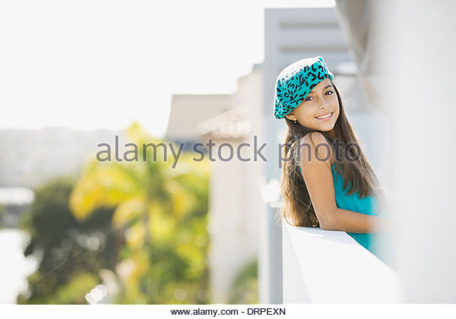 Portrait of girl leaning on balcony - Stock Image