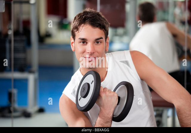 portrait of young man doing weightlifting in gym - Stock Image
