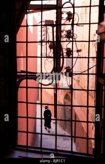 A local man walking up a narrow lane in the medina of Marrakesh - Stock Image