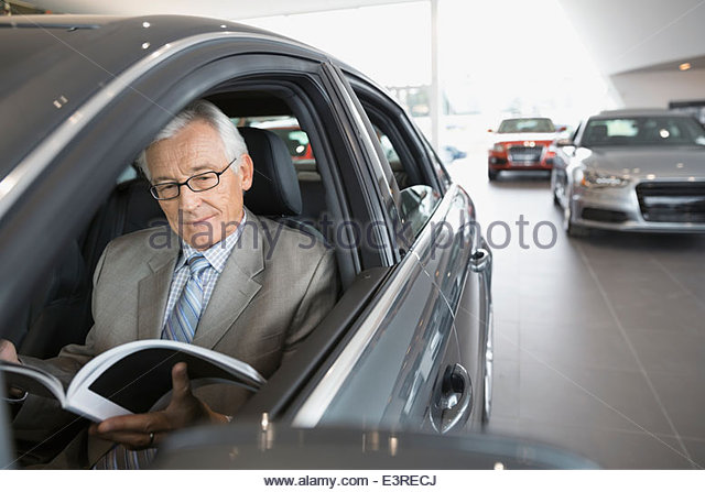 Man with brochure inside car in dealership showroom - Stock Image