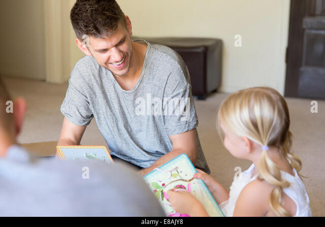 Male couple and daughter threading picture books in sitting room - Stock-Bilder