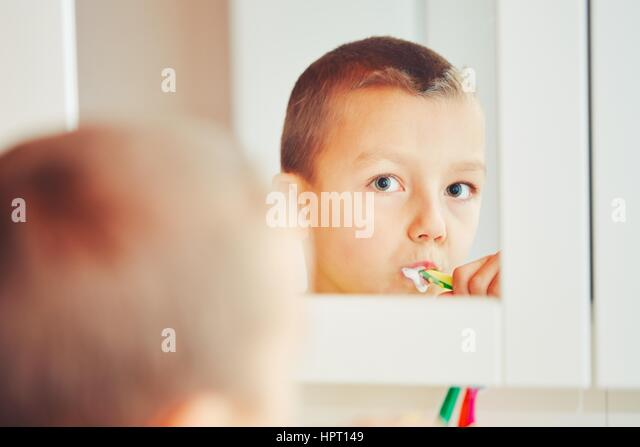 Everyday life at home. Little boy is cleaning teeth in the bathroom. - selective focus - Stock-Bilder