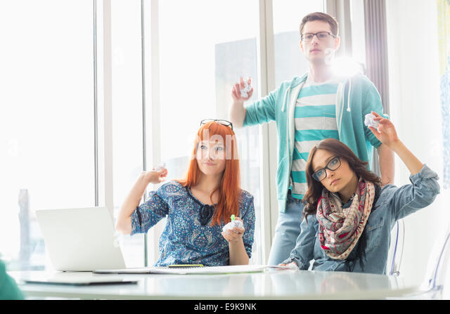 Angry businesspeople throwing paper balls in creative office - Stock Image
