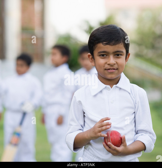 Portrait of a boy holding a cricket ball and smiling - Stock Image
