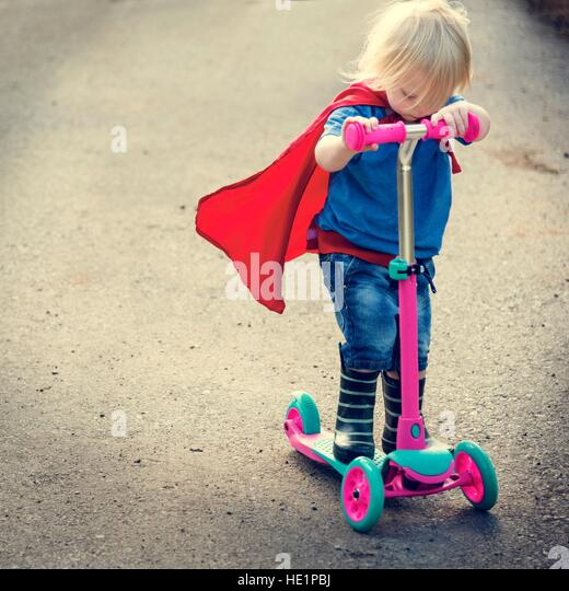 Superhero Baby Boy Using Scooter Adorable Concept - Stock Image