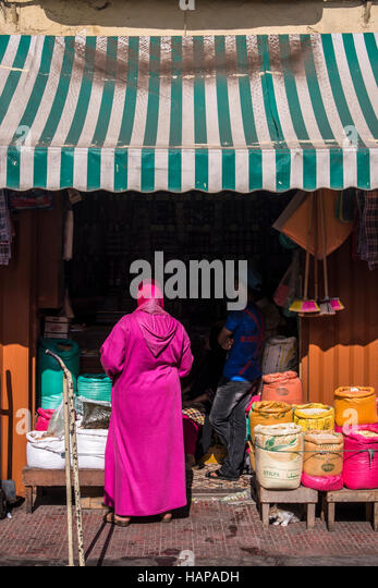 Muslim woman dressed in bright pink Djellaba while waiting to be served on a market shop, selling food, hardware - Stock Image