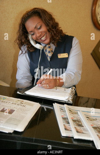 Cleveland Ohio Residence Inn Marriott Black female hotel reservationist front desk telephone - Stock Image