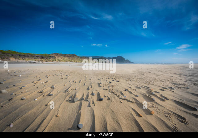 Wispy Clouds Above Stones and Sandy Streaks made from strong winds - Stock Image
