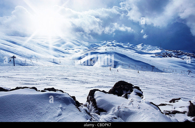 Winter mountain ski resort panoramic landscape with snow, sunny sky & chairlifts - Stock Image