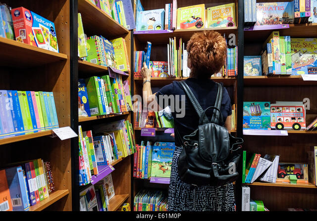Waterstones Bookshop - A woman female mum choosing selecting books for children in a Waterstones bookshop. - Stock Image