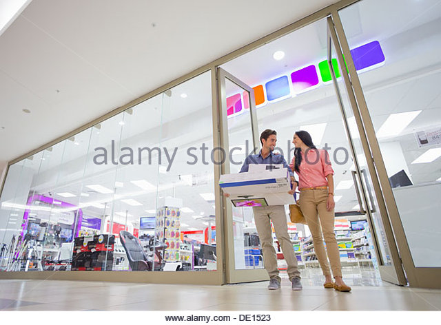 Couple leaving electronics store with boxes - Stock-Bilder