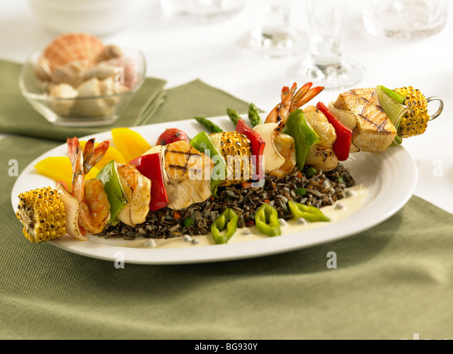 Grilled fish shrimp lobster skewer with vegetables on wild rice - Stock Image