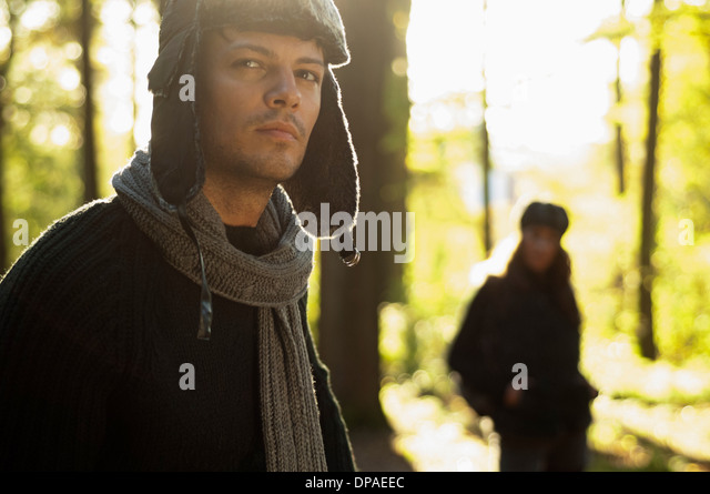 Portrait of mid adult man wearing hat and scarf, woman in background - Stock Image
