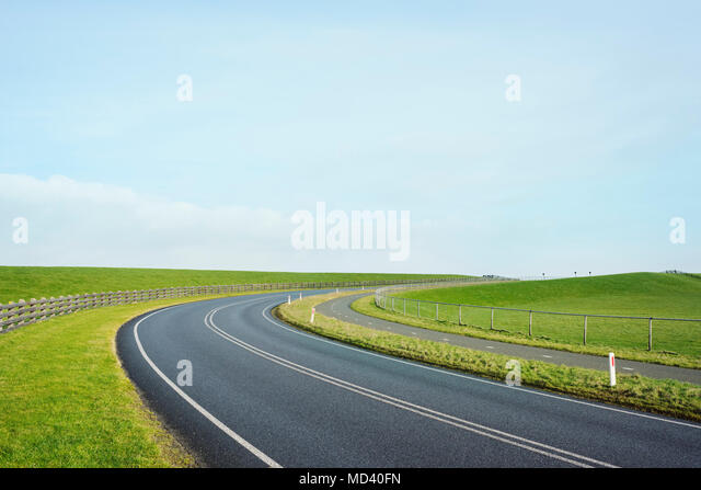 Empty road through the dyke besides the Waddense, Holwerd, Friesland, Netherlands - Stock Image