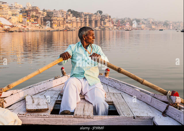 A Indian man rowing a boat for tours on the Ganges river, Varanasi, India. - Stock Image