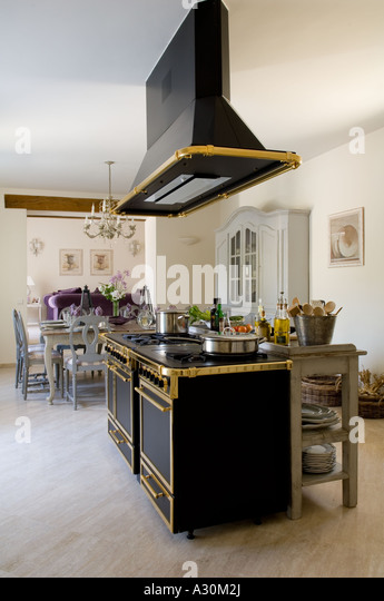 Ornate extractor fan over freestanding gilt plated oven in open plan kitchen - Stock Image