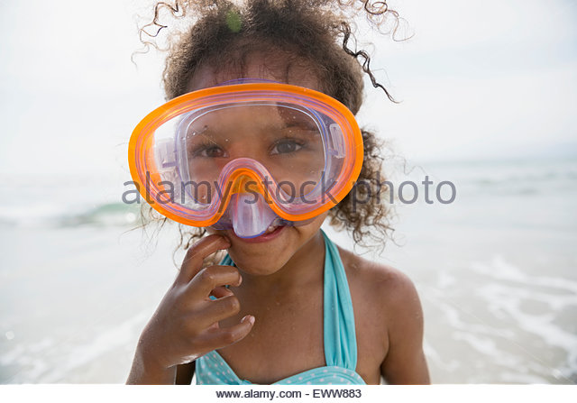 Portrait girl with curly hair in goggles beach - Stock Image