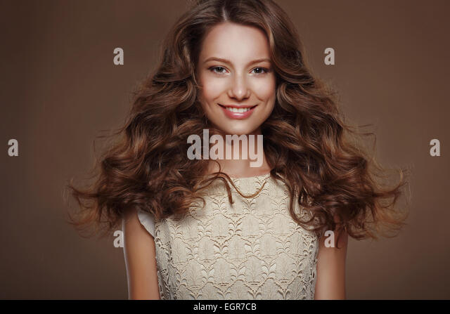 Beautiful Happy Brunette with Long Curly Hairs - Stock Image