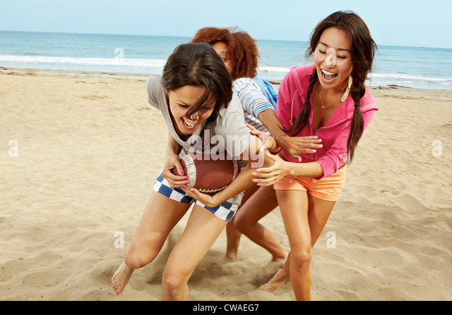 Young female friends playing rugby on beach - Stock Image