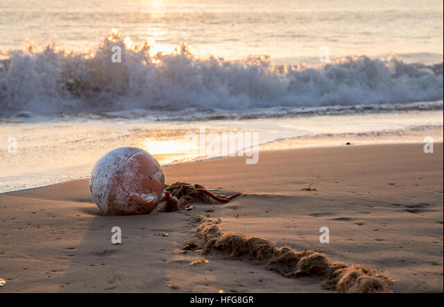 buoy and old worn rope beached in bay at sunrise - Stock Image