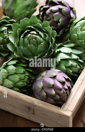 artichokes in wooden box isolated on wooden background - Stock Image