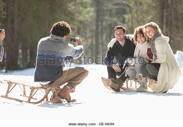 Four friends taking photograph in snowy landscape - Stock Image