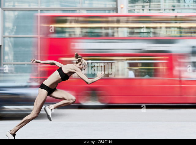 Athlete racing bus on city street - Stock Image