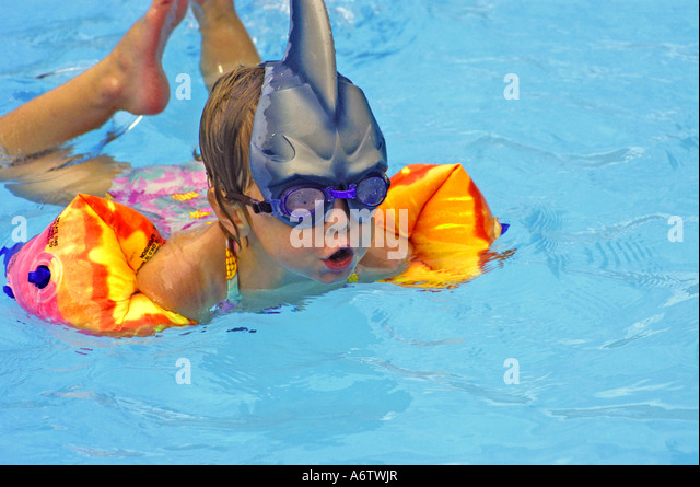 Young girl age 3 learning to swim - Stock Image