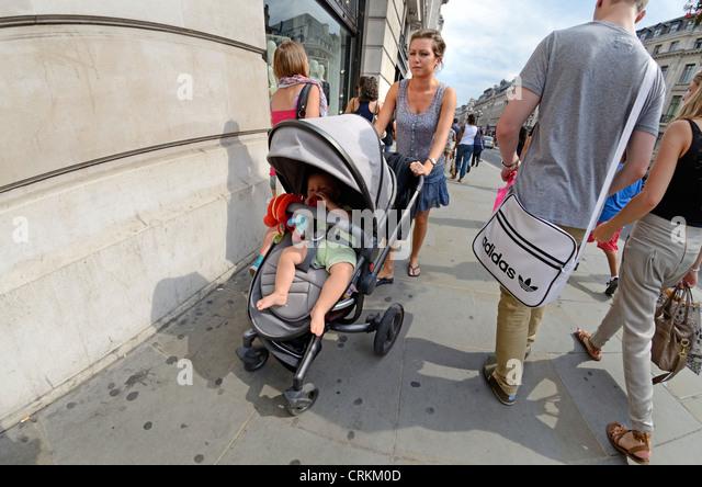 London, England. Young woman pushing baby in pushchair - Stock-Bilder