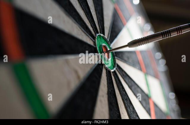 Closeup view of one single dart sticking in the bull's eye of a professional sisal dartboard. Focus on dart - Stock-Bilder