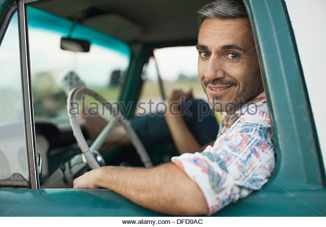 Portrait of mid adult man sitting in pick-up truck - Stock Image